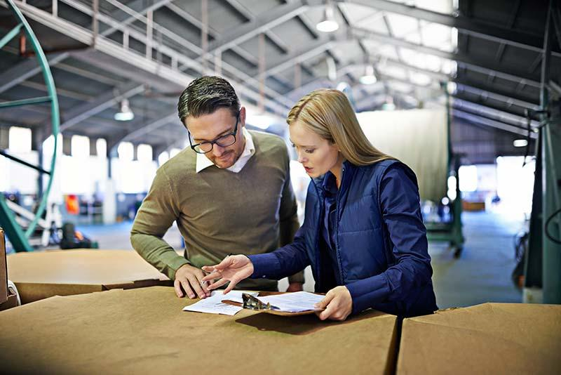 Warehouse managers reviewing inventory